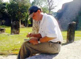 Bob Landstrom studying glyphs on Mayan stele Tikal Guatemala 1999